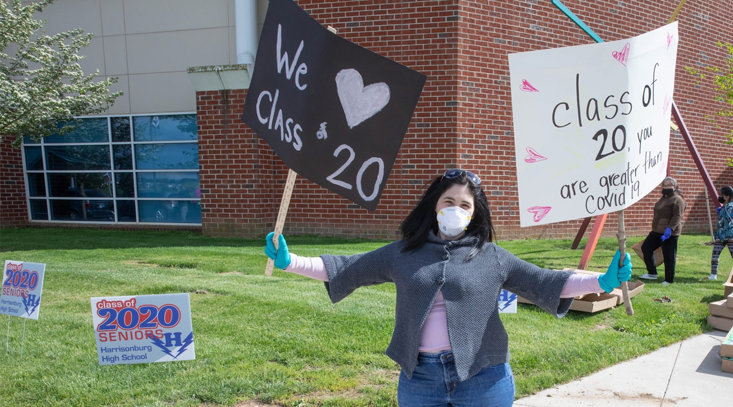 Young woman holding class of 2020 signs